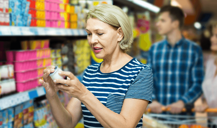 woman looking at labels in grocery aisle