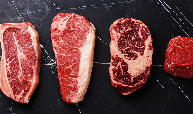 Four different types of aged steaks in a row