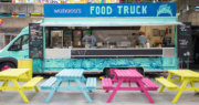 Blue food truck with colorful benches in front